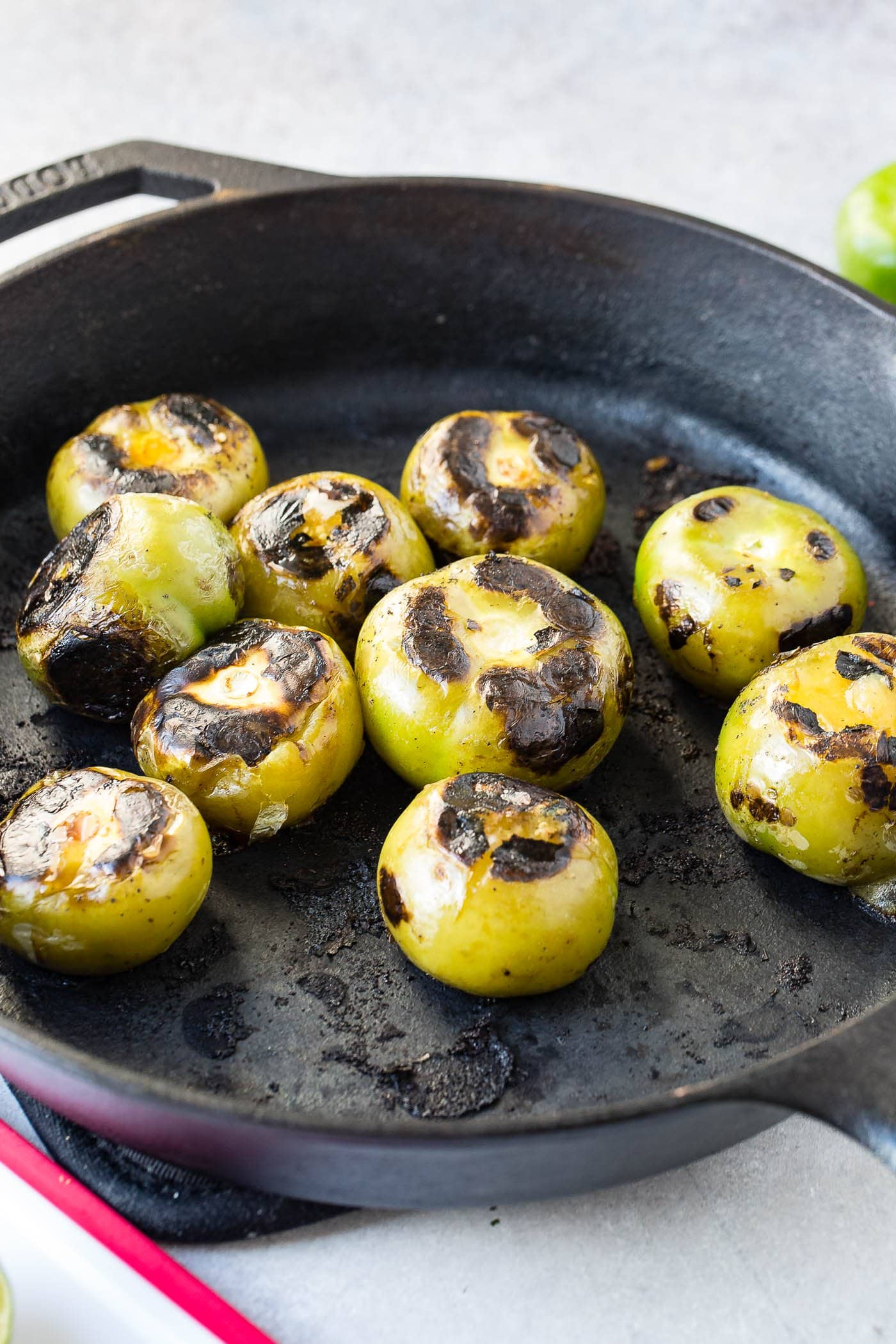 A cast iron skillet with 9 roasted tomatillos.