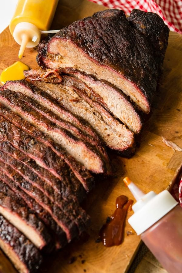 A photo of perfectly smoked brisket sliced and sitting on a wooden cutting board with bottles of BBQ sauce laying next to it.