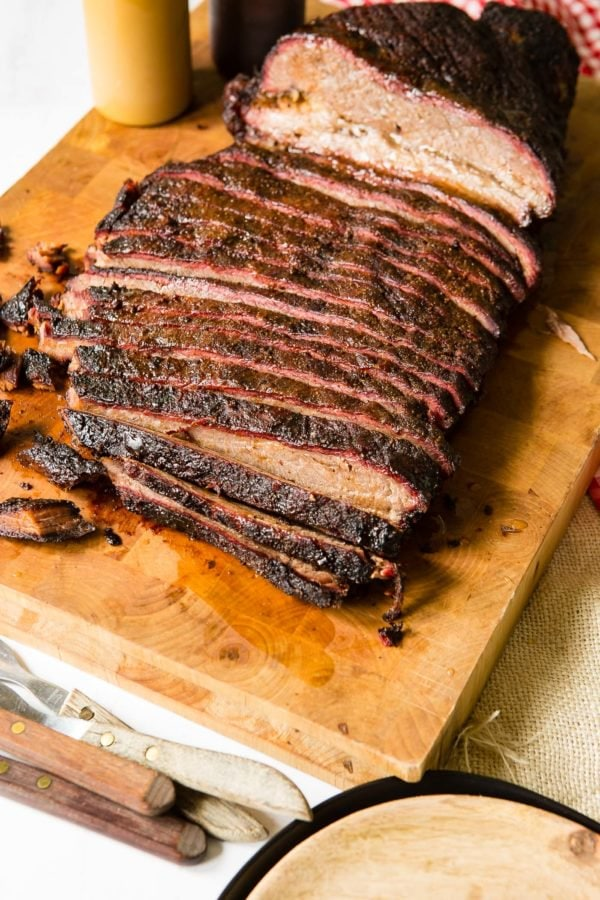 A photo of perfectly smoked brisket sliced on a wooden cutting board.