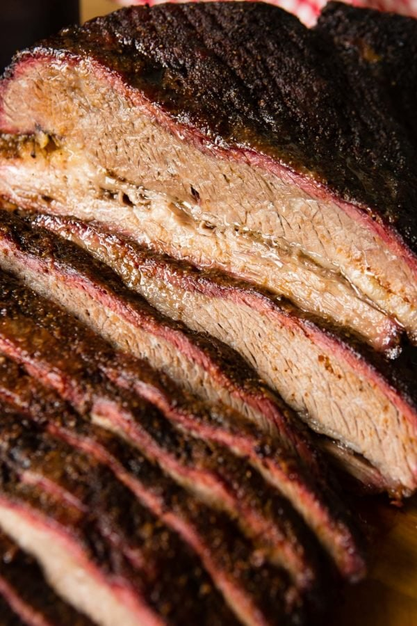 A photo of perfectly smoked brisket sliced with a beautiful smoke ring.