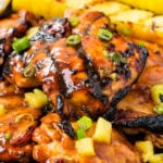 A photo of grilled huli huli chicken with grilled pineapple in the background.