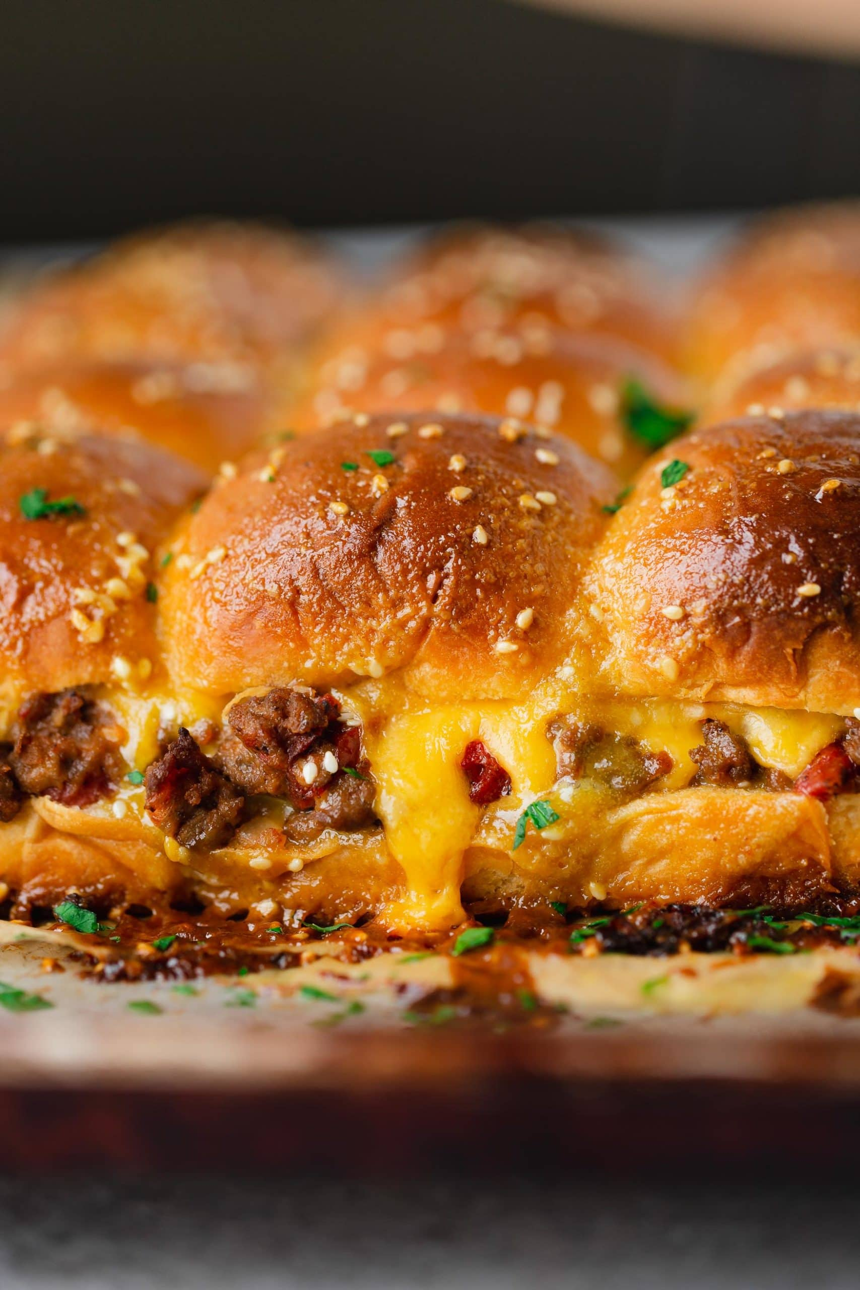 A panful of cheeseburger sliders. There is ground beef, chopped tomatoes and melted cheese on the buns and the buns are topped with sesame seeds and sauce.