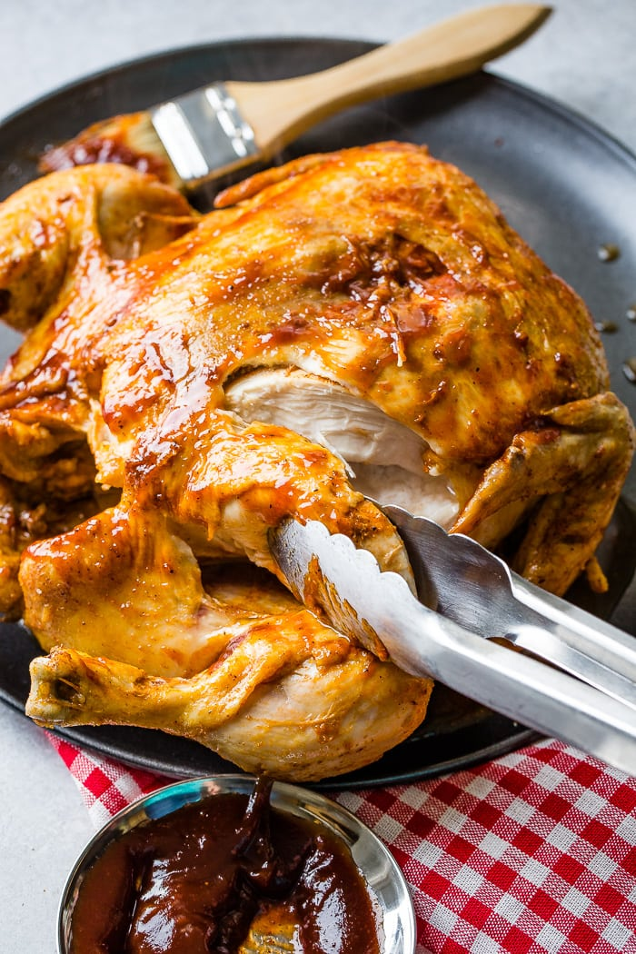 A red and white checkered napkin under a grey plate with a bbq instant pot whole chicken on top!