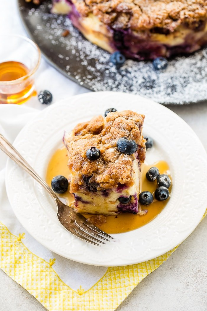 Blueberries on a piece of french toast bake or french toast casserole with maple syrup and a sprinkle of powdered sugar for a breakfast or brunch recipe with a vintage fork and white lace plate with maple syrup in the background.