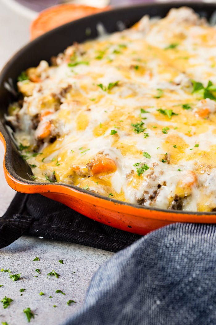 A photo cheesy ground beef and rice casserole in an orange cast iron skillet topped with melted cheesy and chopped fresh parsley.