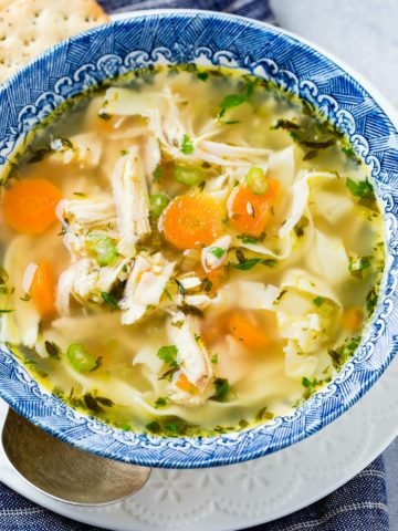 A photo of a bowl of homemade chicken noodle soup full of carrots, celery, chicken, pasta, and herbs.