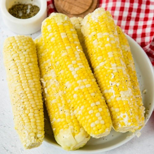 A serving plate with 5 ears of corn. The plate of corn is sitting on a red and white checked tea towel and there is a small container of fresh ground pepper in the background.