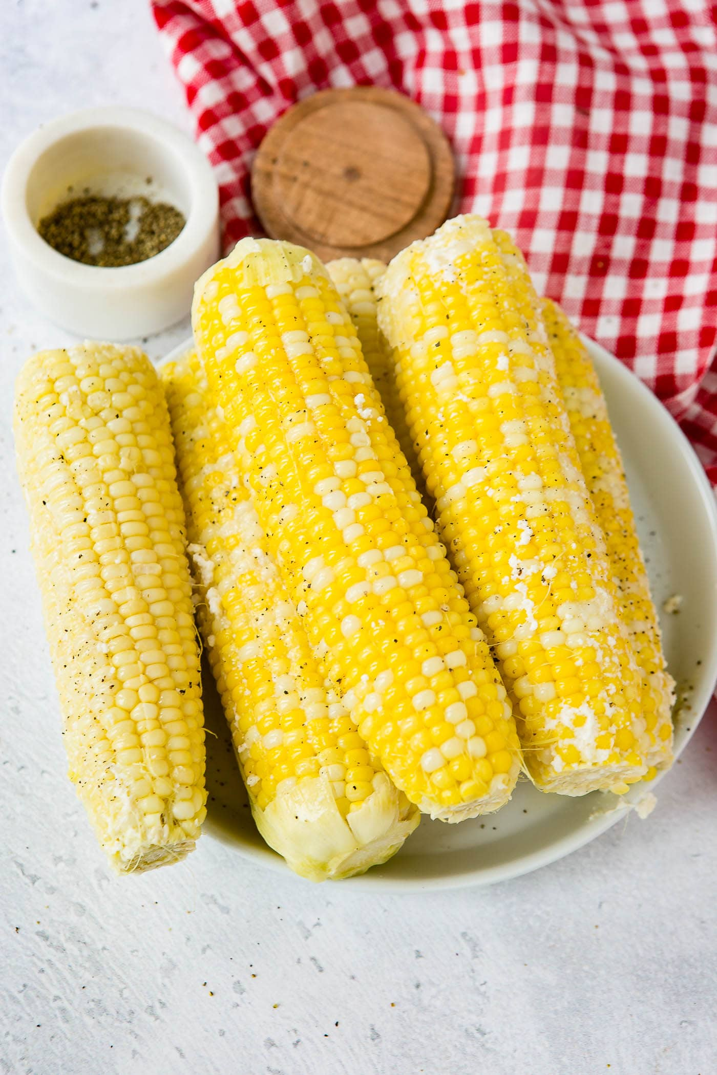 A serving plate with 5 ears of corn. The plate of corn is sitting on a red and white checked tea towel and there is a small container of