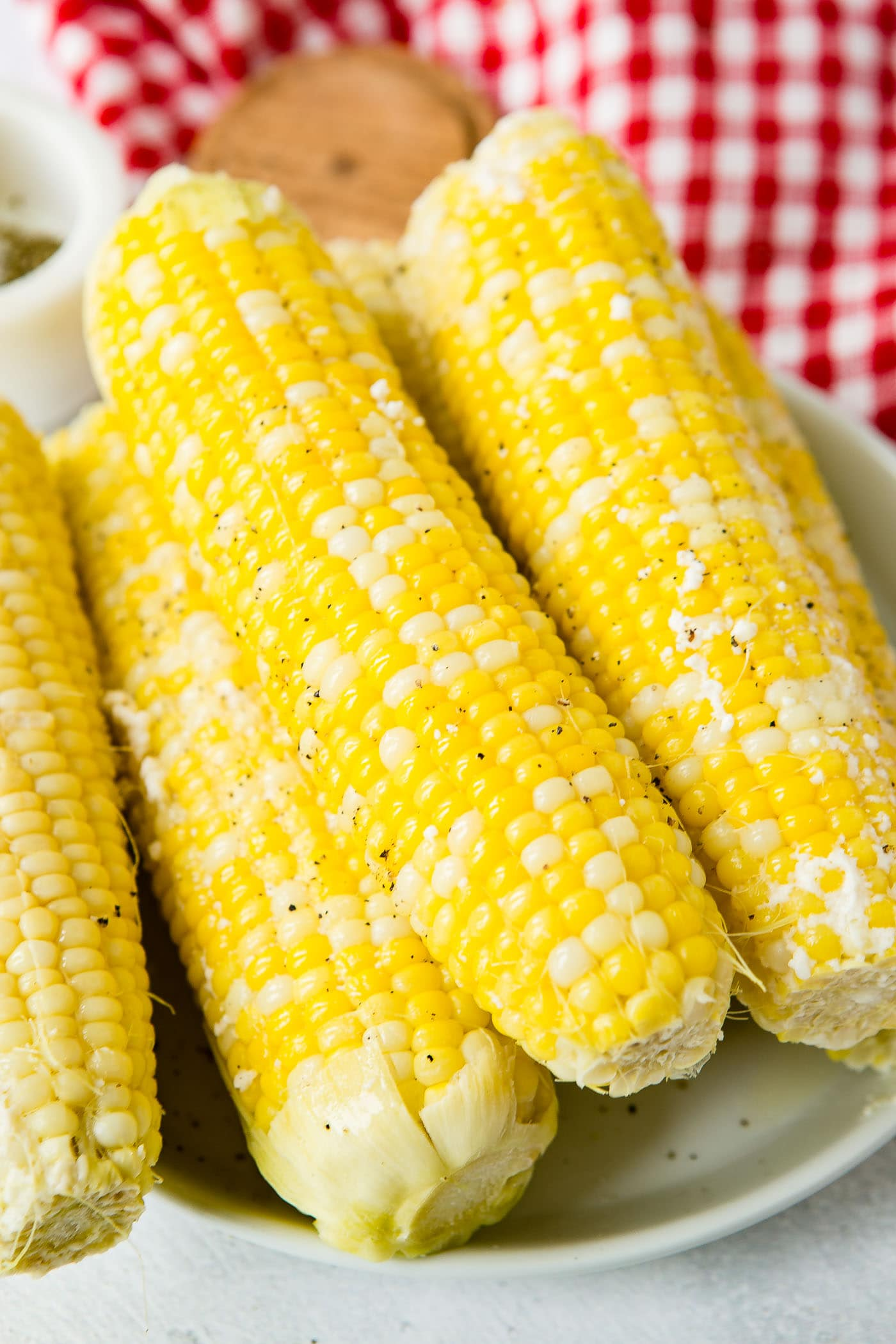 Four ears of cooked corn on the cob. The plate of corn is sitting on a red checked tea towel.