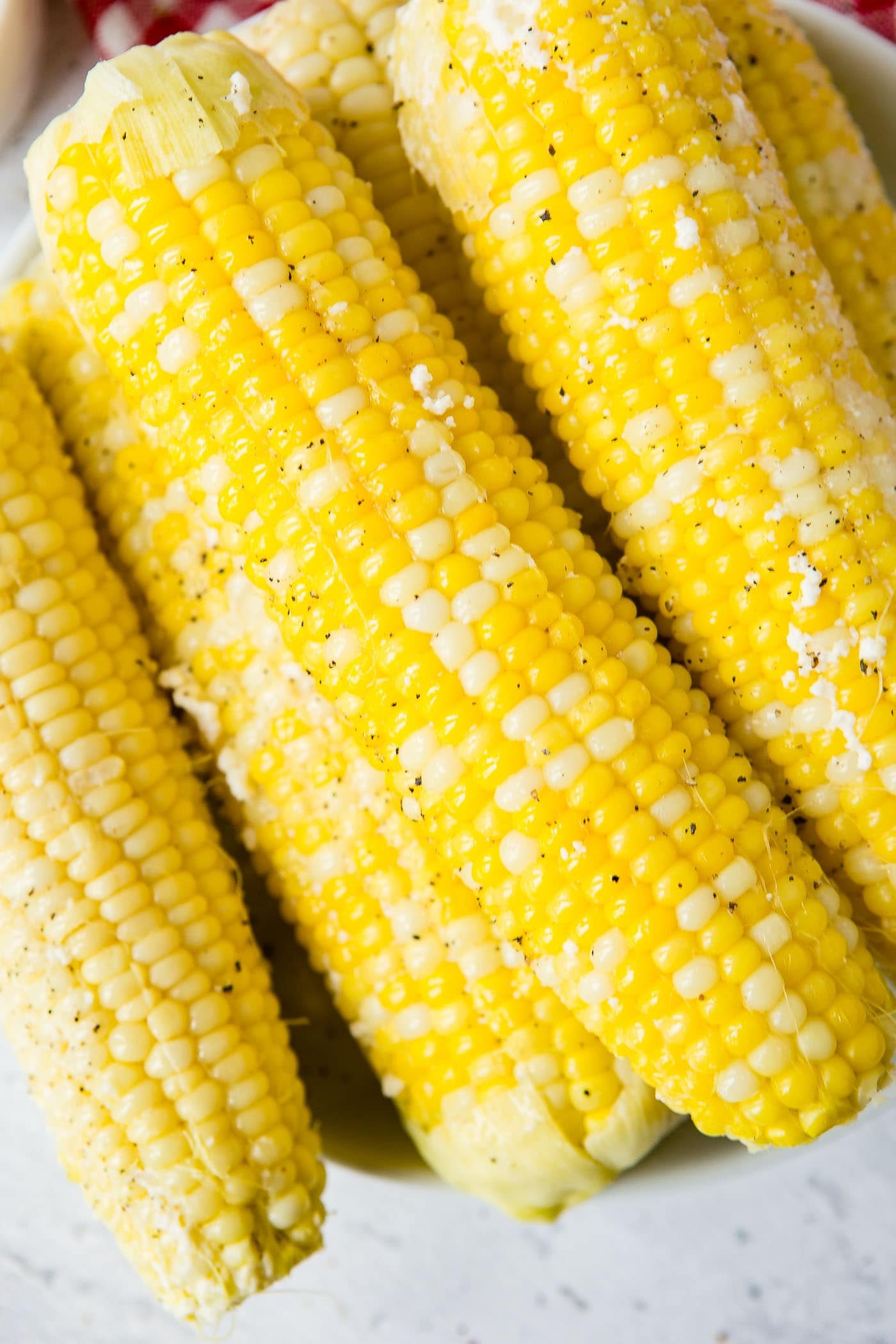 A close-up of four ears of cooked corn on the cob sprinkled with ground pepper.