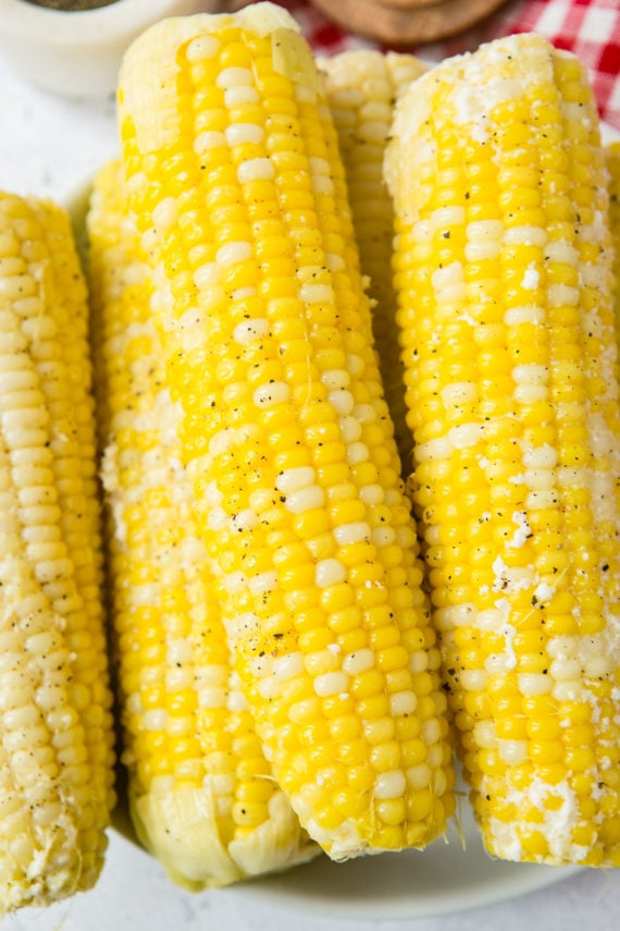 Four ears of cooked corn on the cob that has been lightly sprinkled with ground pepper.