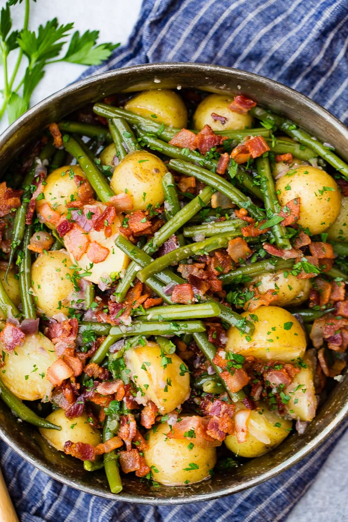 A silver serving dish sitting on a blue cloth napkin that is full of cooked fresh green beans, potatoes, and bacon pieces sprinkled with fresh parsley.