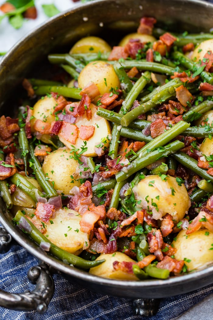 A photo of a silver serving dish sitting on a blue cloth napkin that is full of cooked fresh green beans, potatoes, and bacon pieces sprinkled with fresh parsley.