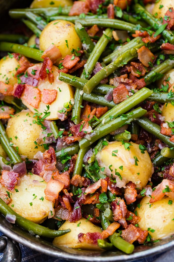a zoomed in photo of cooked green beans, potatoes, and bacon pieces sprinkled with fresh parsley.