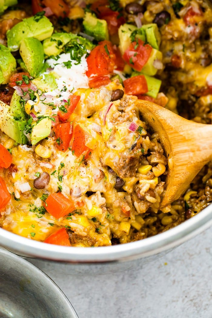 A photo of instant pot ground beef burrito bowl stopped with chopped tomatoes, avocado chunks, and chopped fresh cilantro and a wooden spoon taking a scoop out.