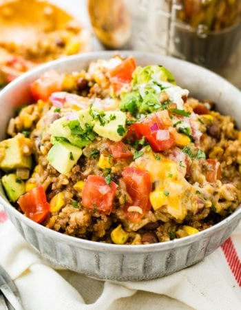 A photo of instant pot ground beef burrito bowl stopped with chopped tomatoes, avocado chunks, and chopped fresh cilantro.