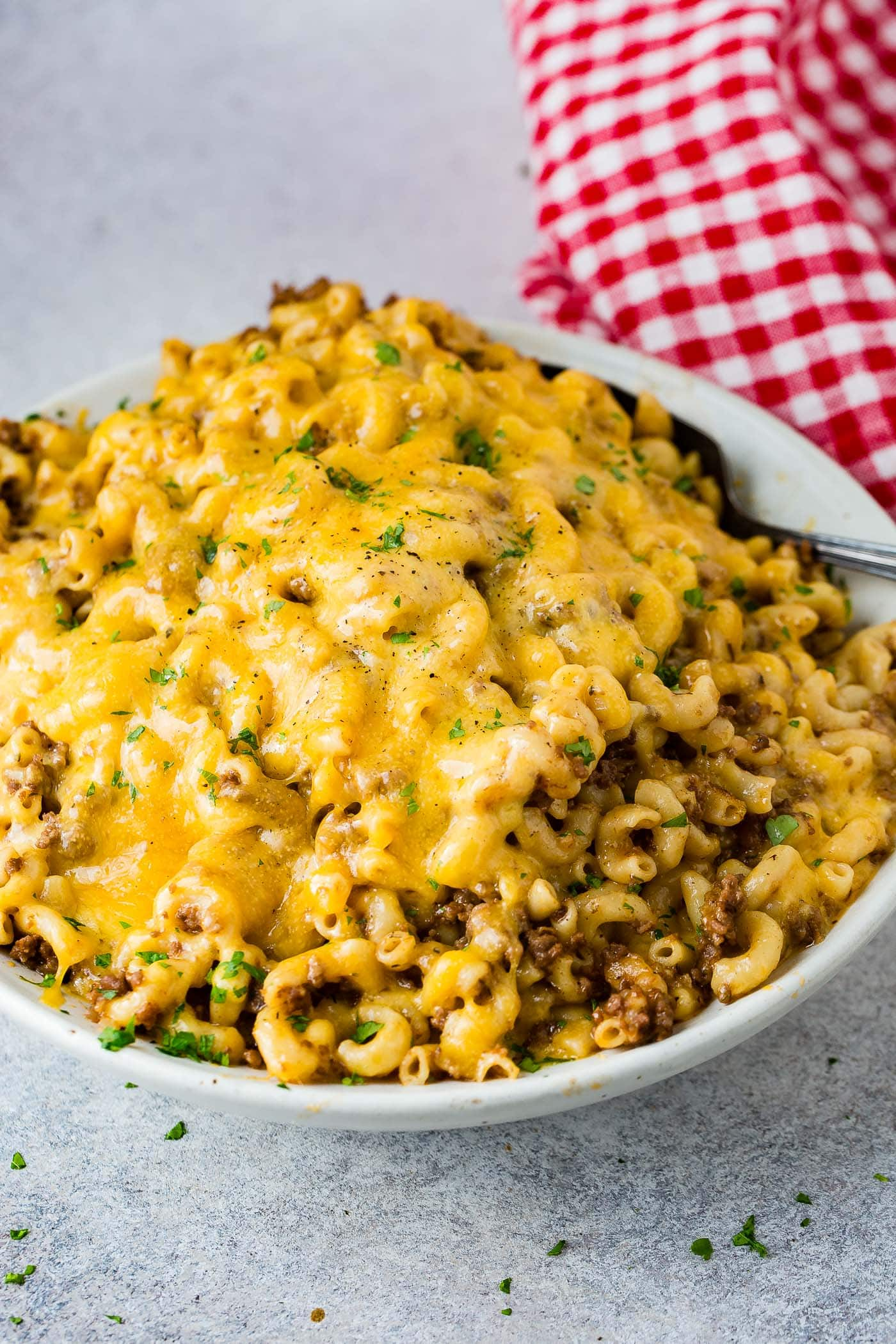 A photo of a white serving bowl full of cheesy Hamburger Helper ready to serve.