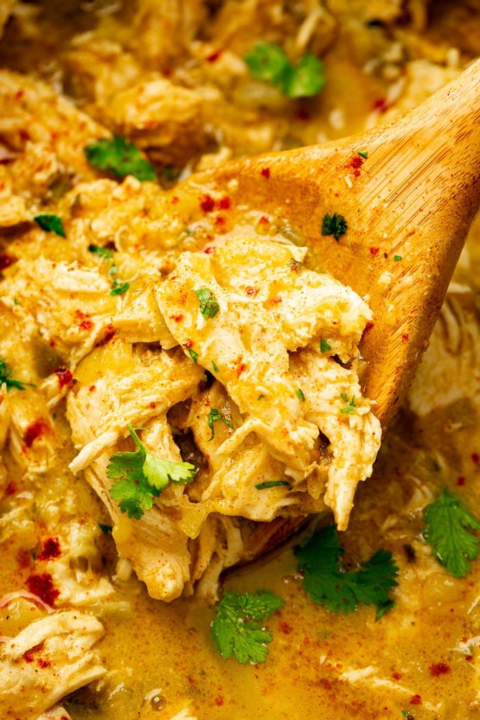 a slow cooker full of shredded chicken in a salsa verde pineapple sauce