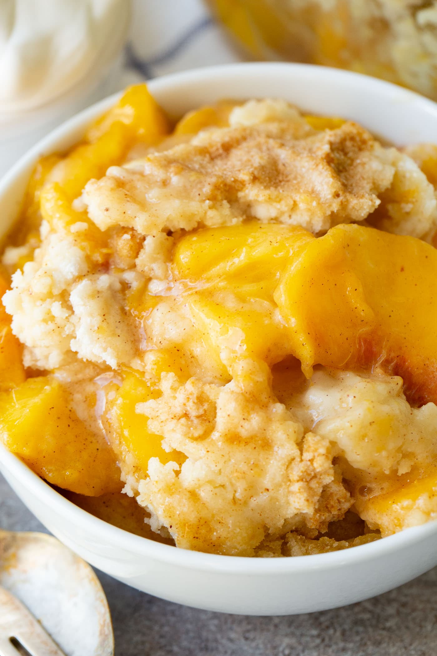 a bowl of instant pot peach cobbler with cake mix topping
