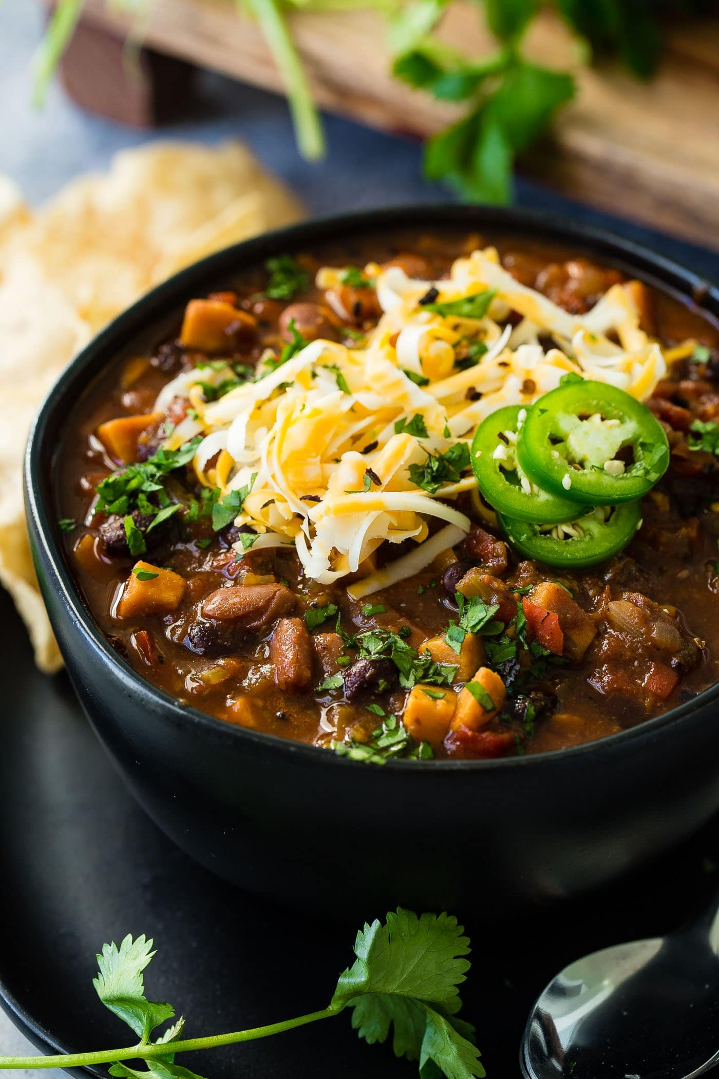 A photo of a bowl of vegetarian chili topped with shredded cheese and slices of fresh jalapeno.