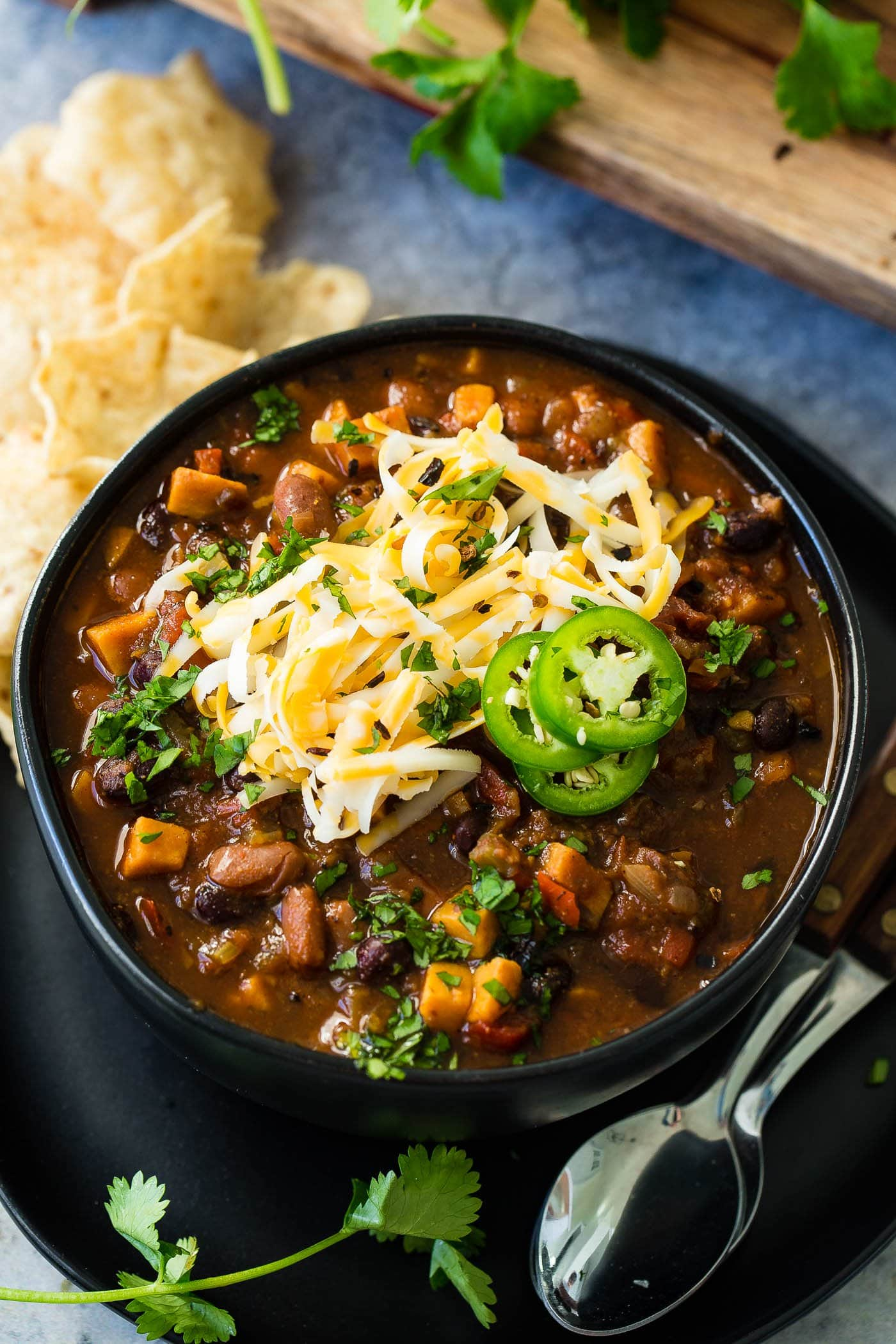 A photo of a bowl of hearty vegetarian chili topped with shredded cheese and sliced jalapeno.