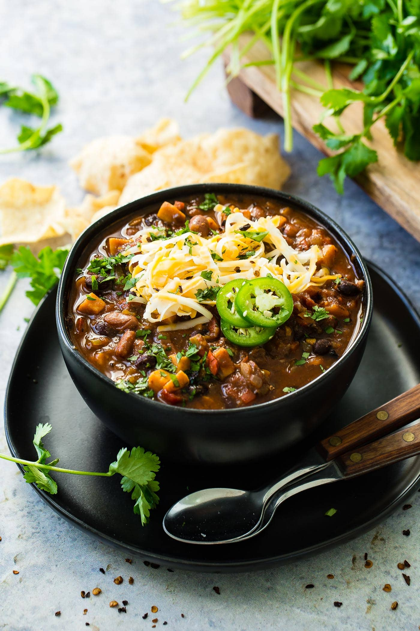 A photo of a bowl of hearty vegetarian chili topped with shredded cheese and sliced jalapeno with two spoons sitting next to the bowl.