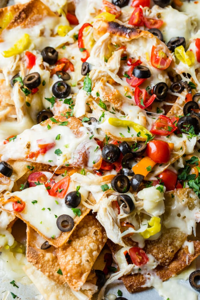 A close up of Italian Nachos with olives, chicken, cheese, alfredo and peppers!