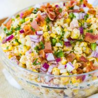A bowl of Mexican corn salad topped with bacon and jalapeno.