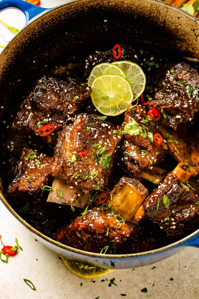 A photo of several braised short ribs still in the dutch oven garnished with sesame seeds, red chile peppers, cilantro, green onions, and lime slices.