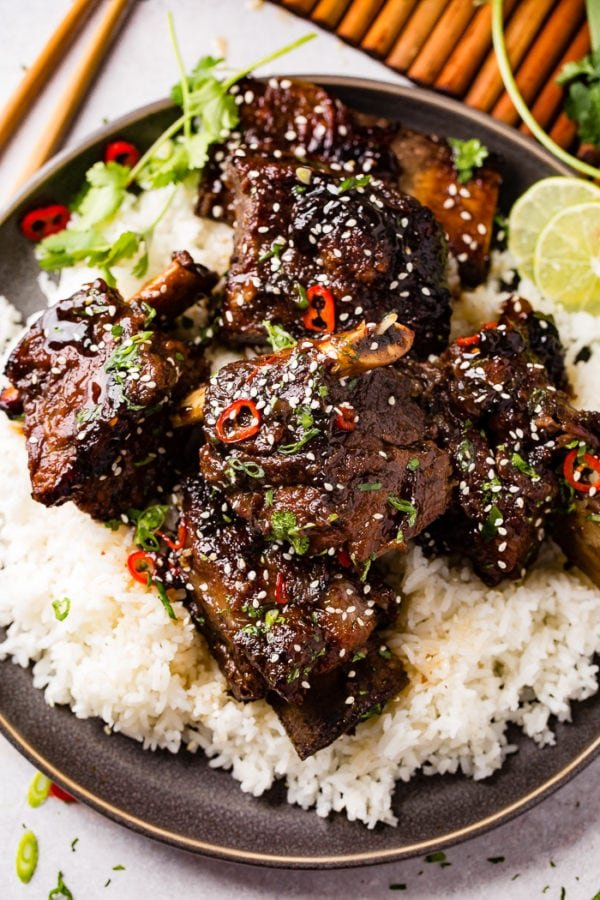 A photo of braised short ribs garnished with sesame seeds, cilantro, green onion and red chile peppers on top of white rice on a gray plate. This can be made into a freezer meal for meal prep.