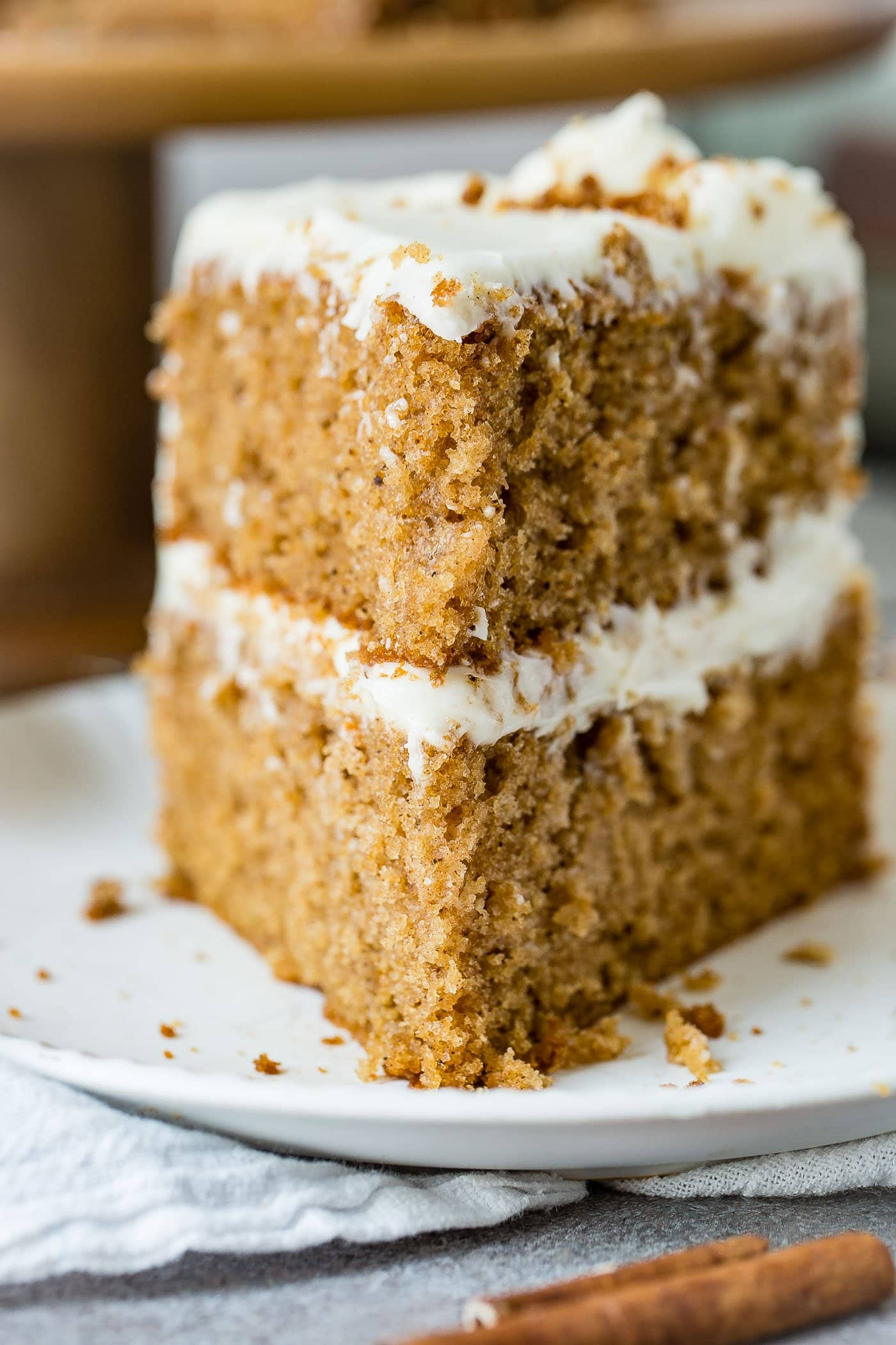 A slice of spice cake. There are two layers with cream cheese frosting between the layers and on top of the cake.