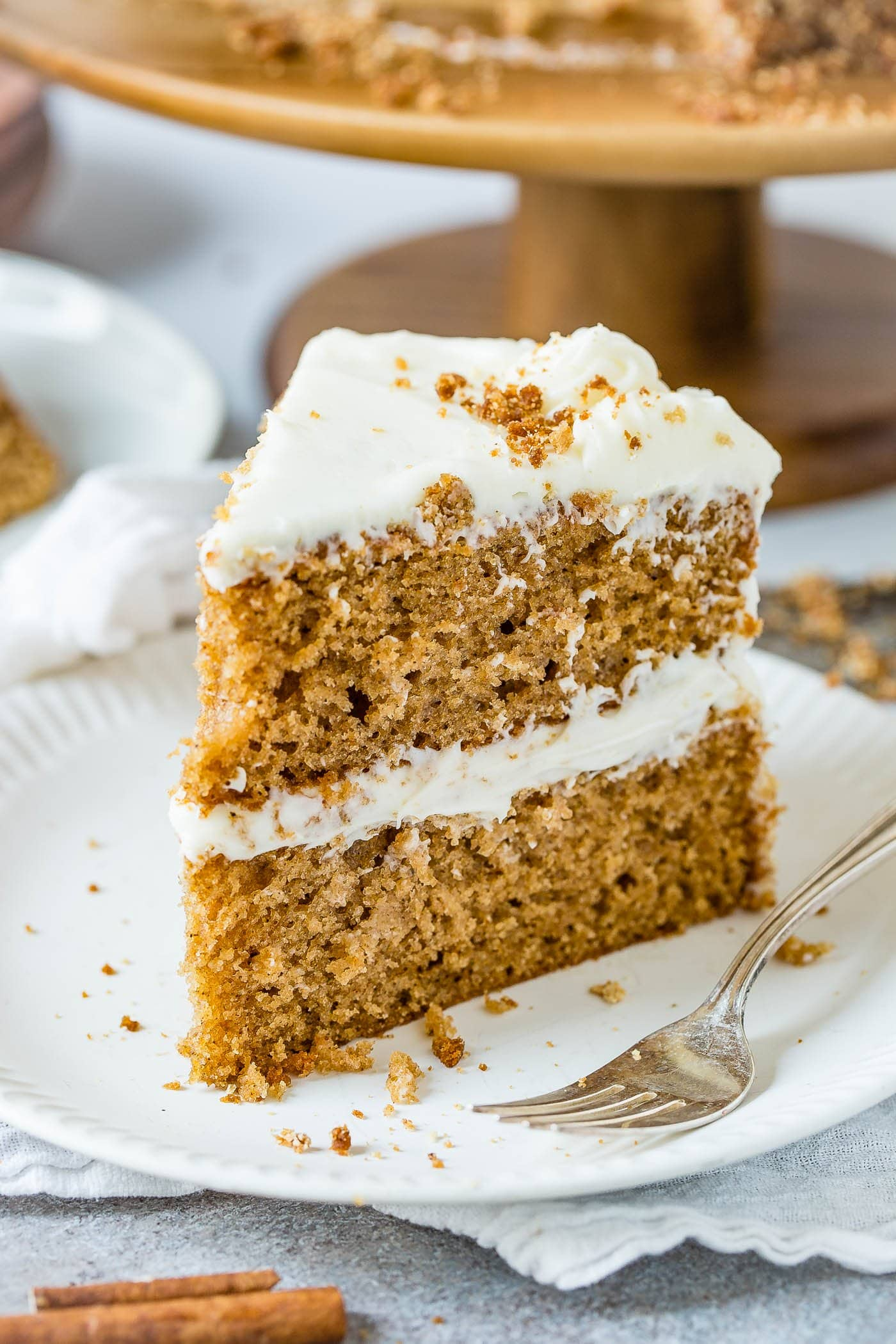 A slice of two layer spice cake frosted with cream cheese frosting. The cake is on a white dessert plate with a fork next to it.