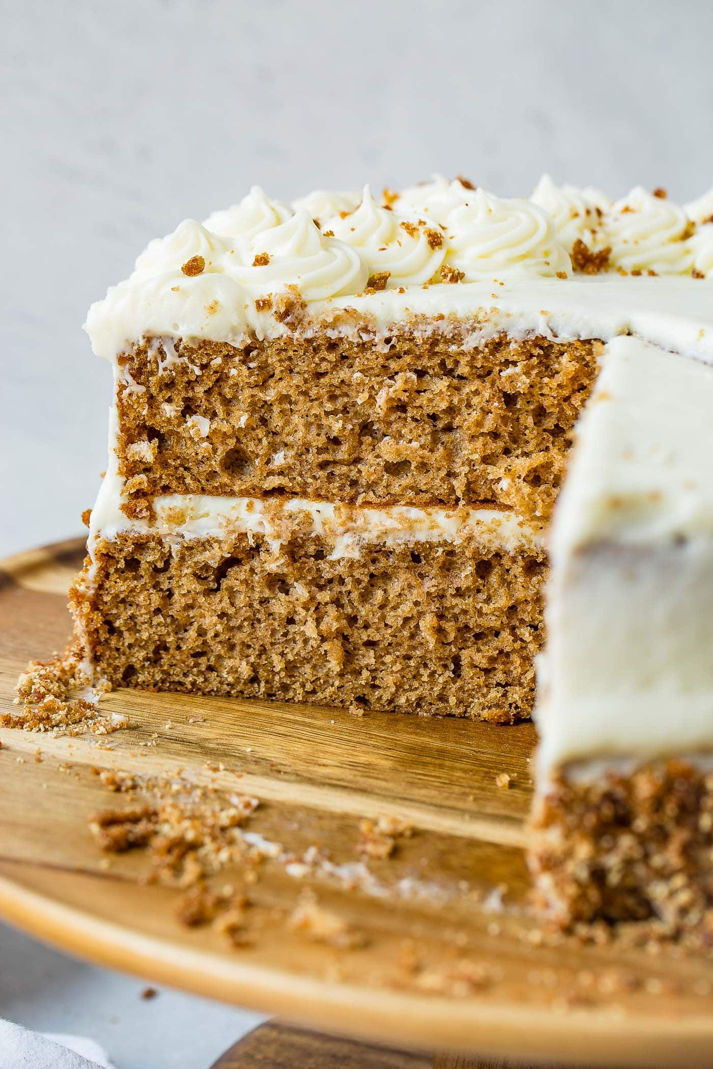 A two layer cake with whipped cream between layers and on top. A slice has been cut out of the cake.