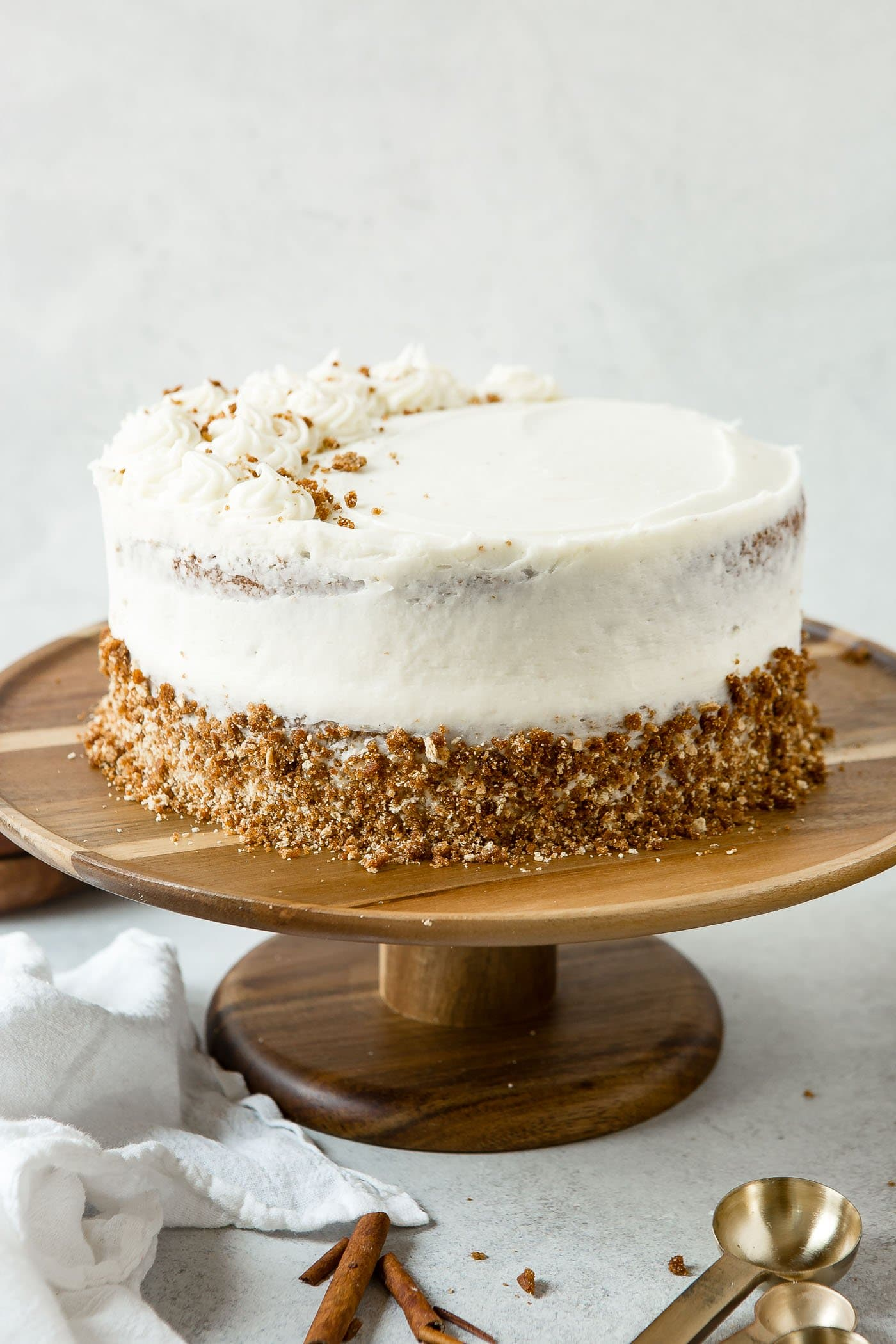 A two layer spice cake on a cake plate. The cake is frosted with cream cheese frosting. frosting
