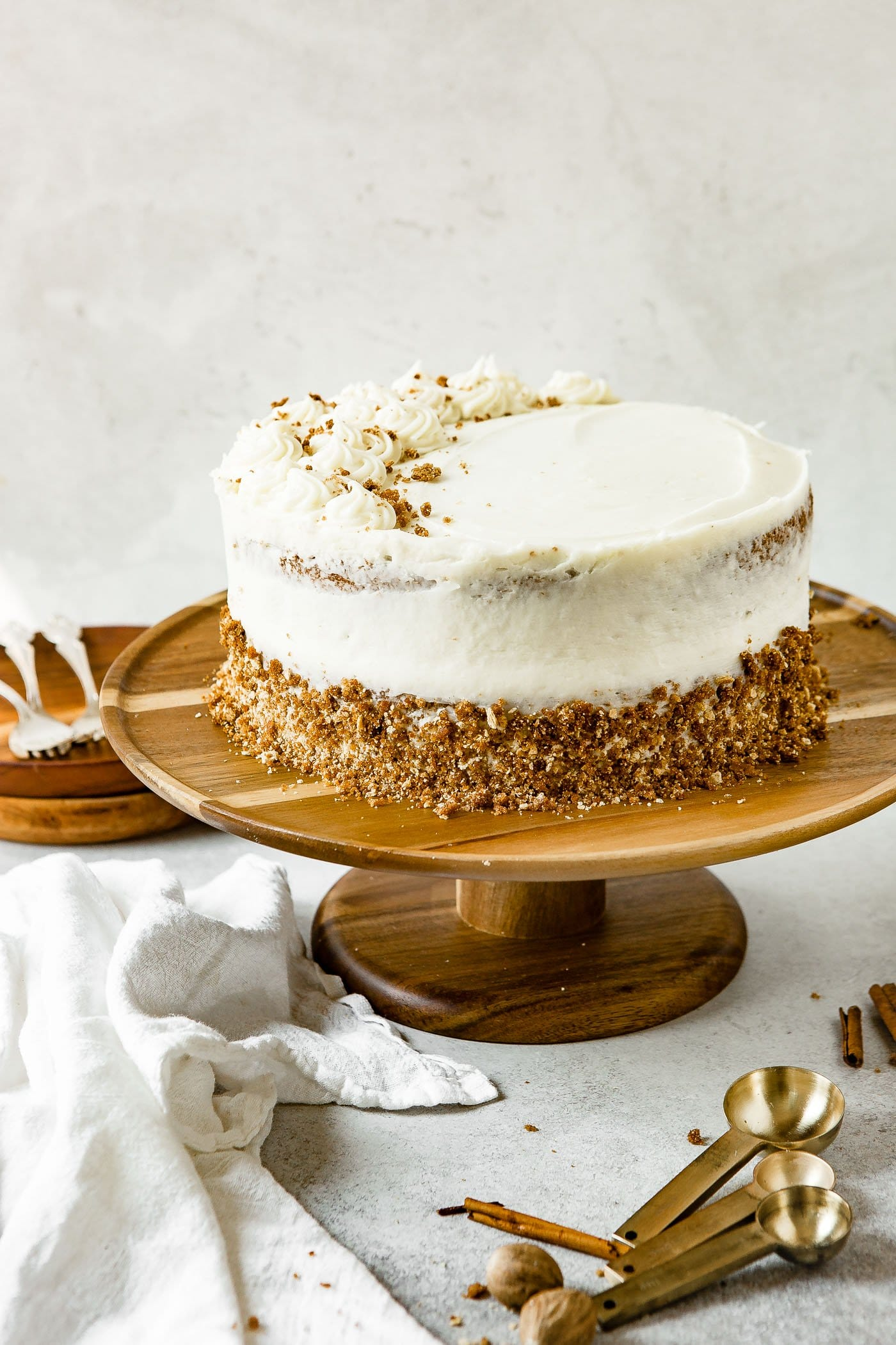 A two layered spice cake on a cake plate. The cake is frosted with cream cheese frosting and the bottom layer is rolled in a crumb mixture.