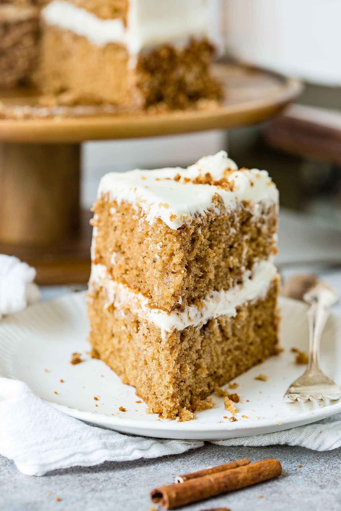 A slice of two layer spice cake with cream cheese frosting. It is on a white plate with a fork next to the cake. A cake plate with the rest of the cake is in the background.