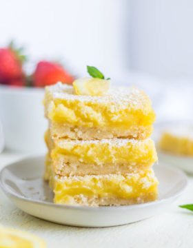 A white plate stacked with bright yellow classic lemon bars recipe and strawberries in a dish behind it