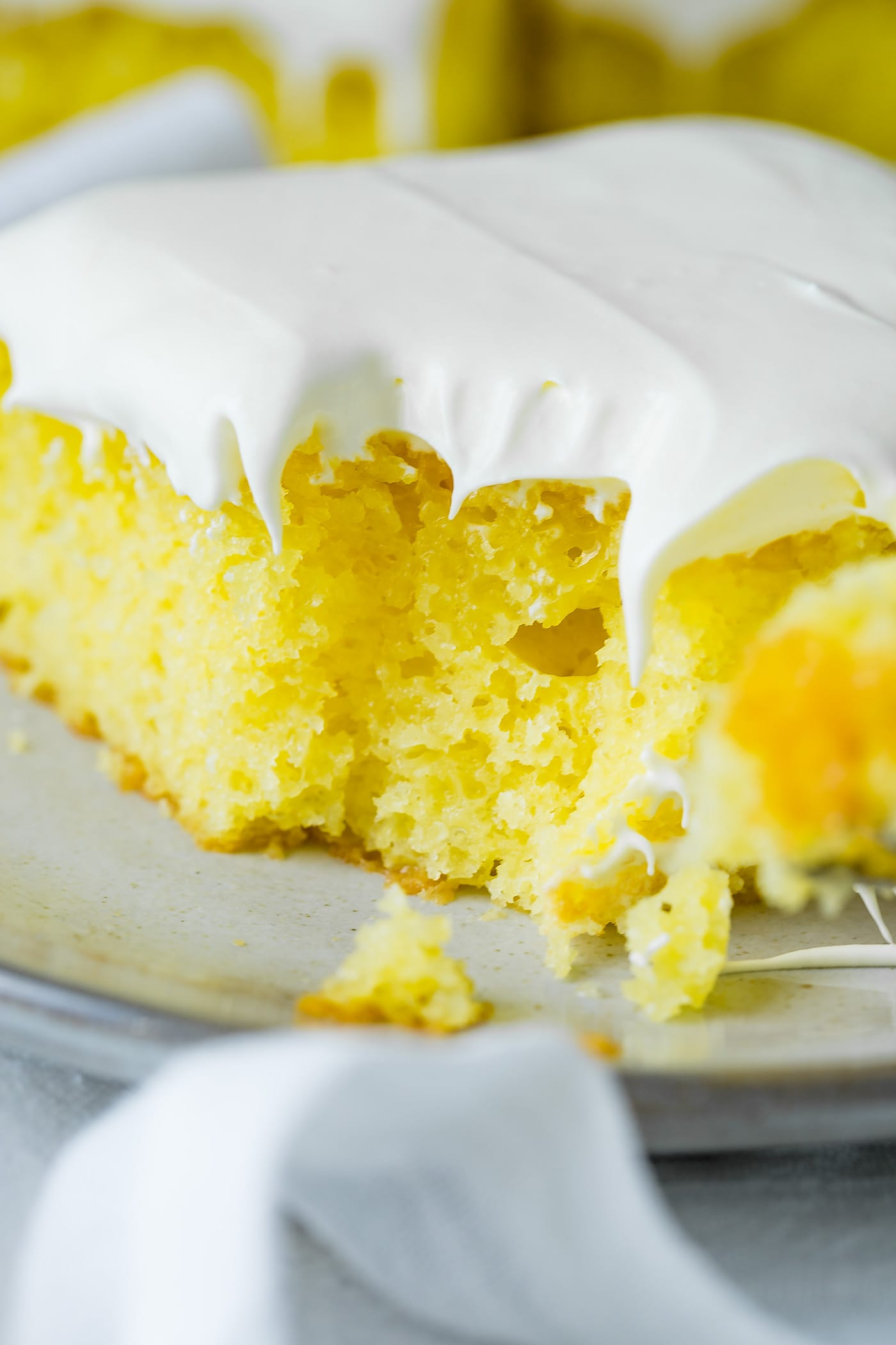 A slice of bright yellow lemon jello cake with fluffy white frosting on top. A bite has been taken from the corner of the cake.