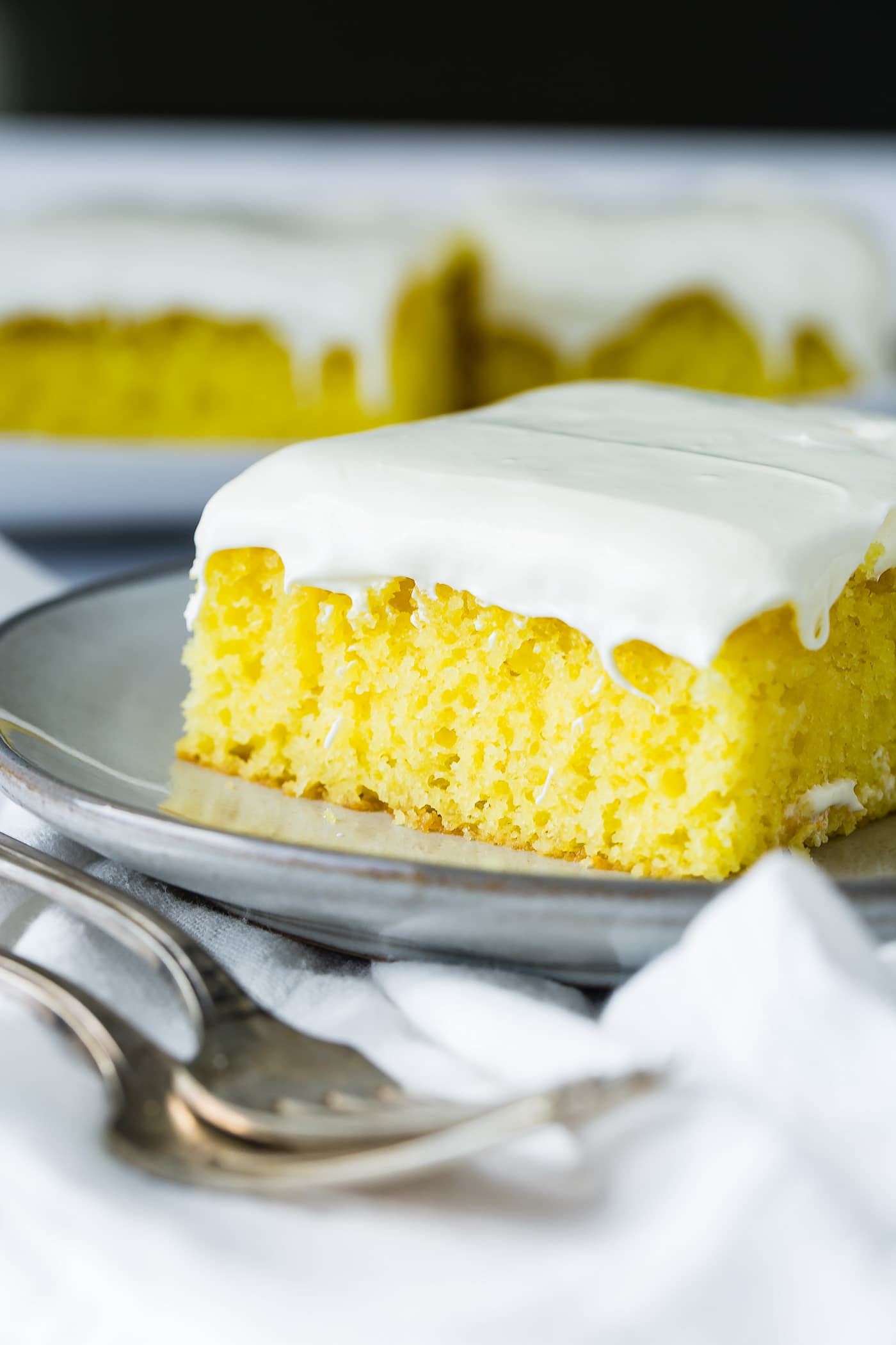 A slice of frosted lemon jello cake on a serving plate with a couple of slices on another plate in the background. There are two forks resting on a white linen napkin next to the plate of cake.