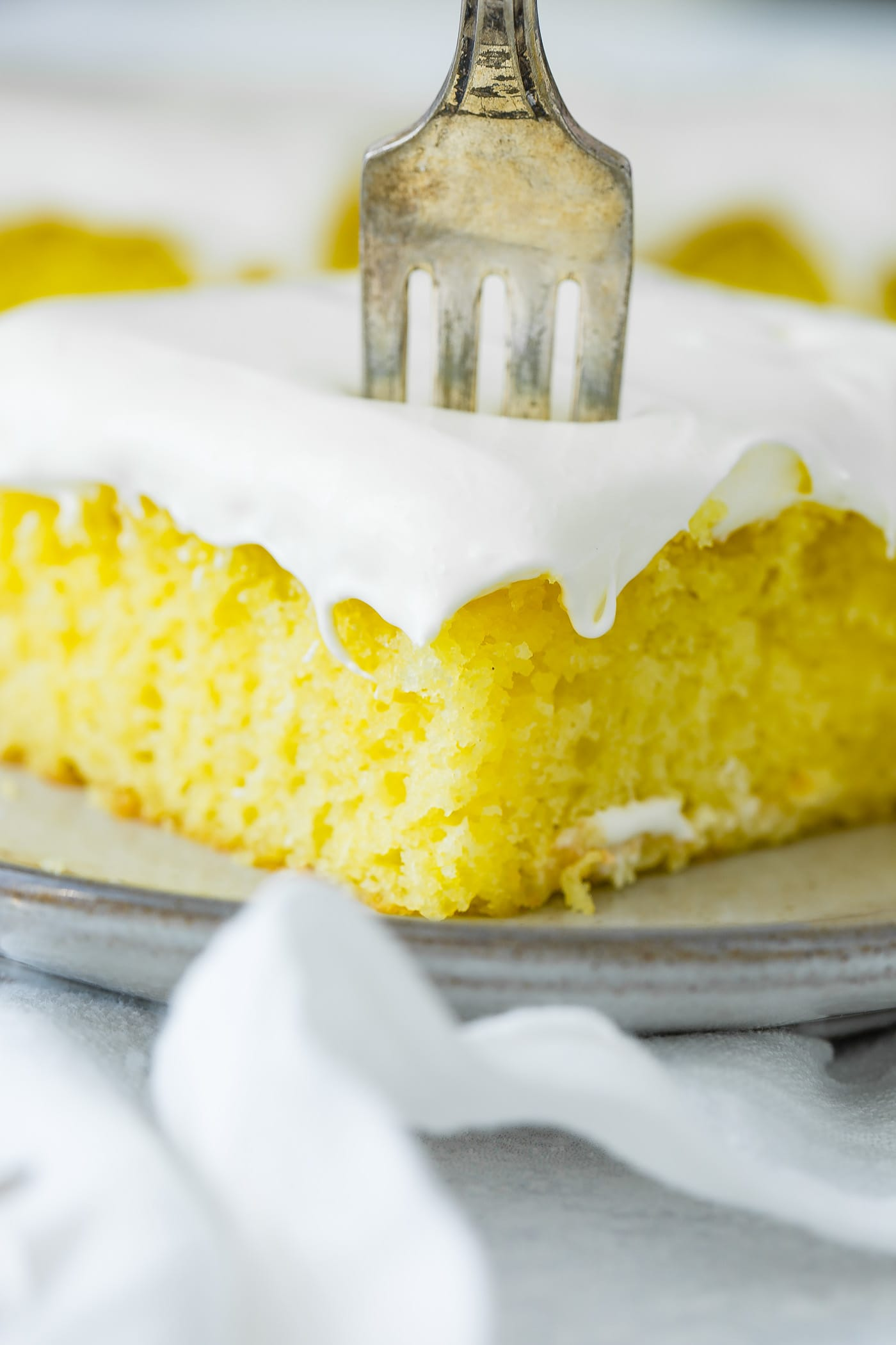 A slice of frosted lemon jello cake with a fork sticking into the top. It is on a serving plate which is sitting on a white linen napkin.