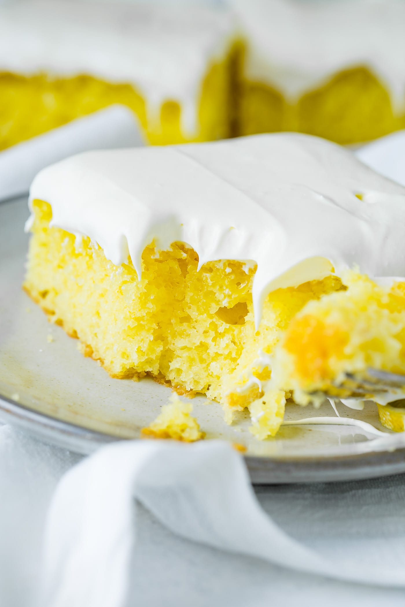 A slice of yellow lemon jello cake with a bite taken from the corner. It is topped with a fluffy white frosting and rests on a serving plate on top of a white linen napkin.
