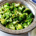 A vintage silver bowl with lemon roasted broccoli with pine nuts and parmesan cheese