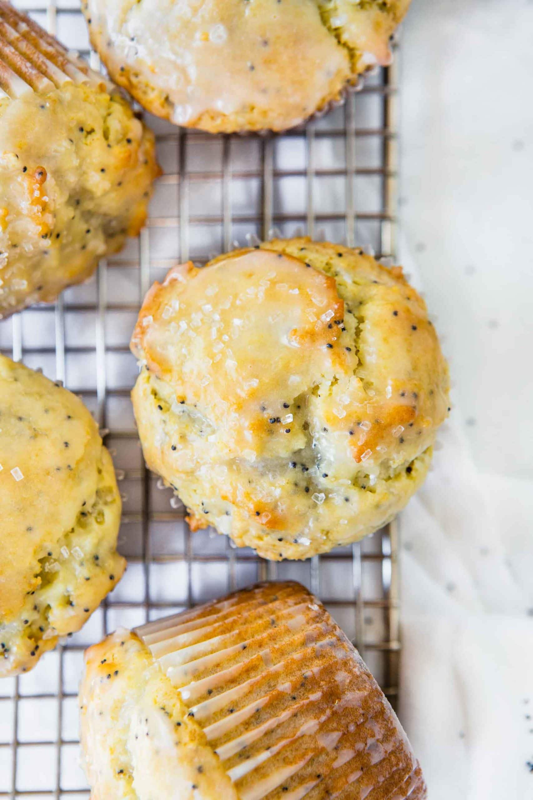 Lemon poppy seed muffins sitting on a wire cooling rack. They have a lemon glaze on top.