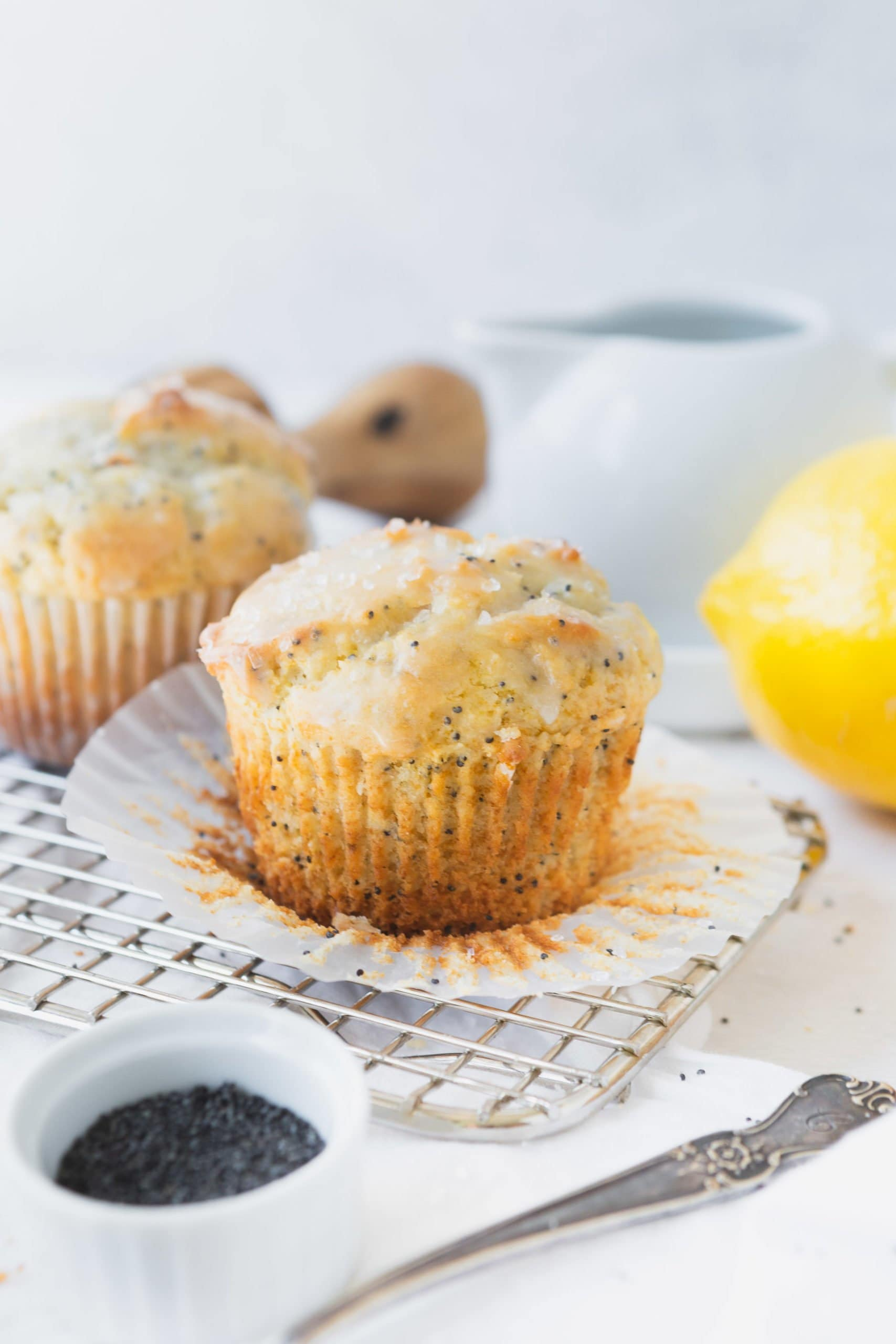A lemon poppy seed muffin that has the paper liner peeled back. The muffin is glazed with a lemon glaze and there is another muffin and a lemon, a container of poppy seeds in the background.