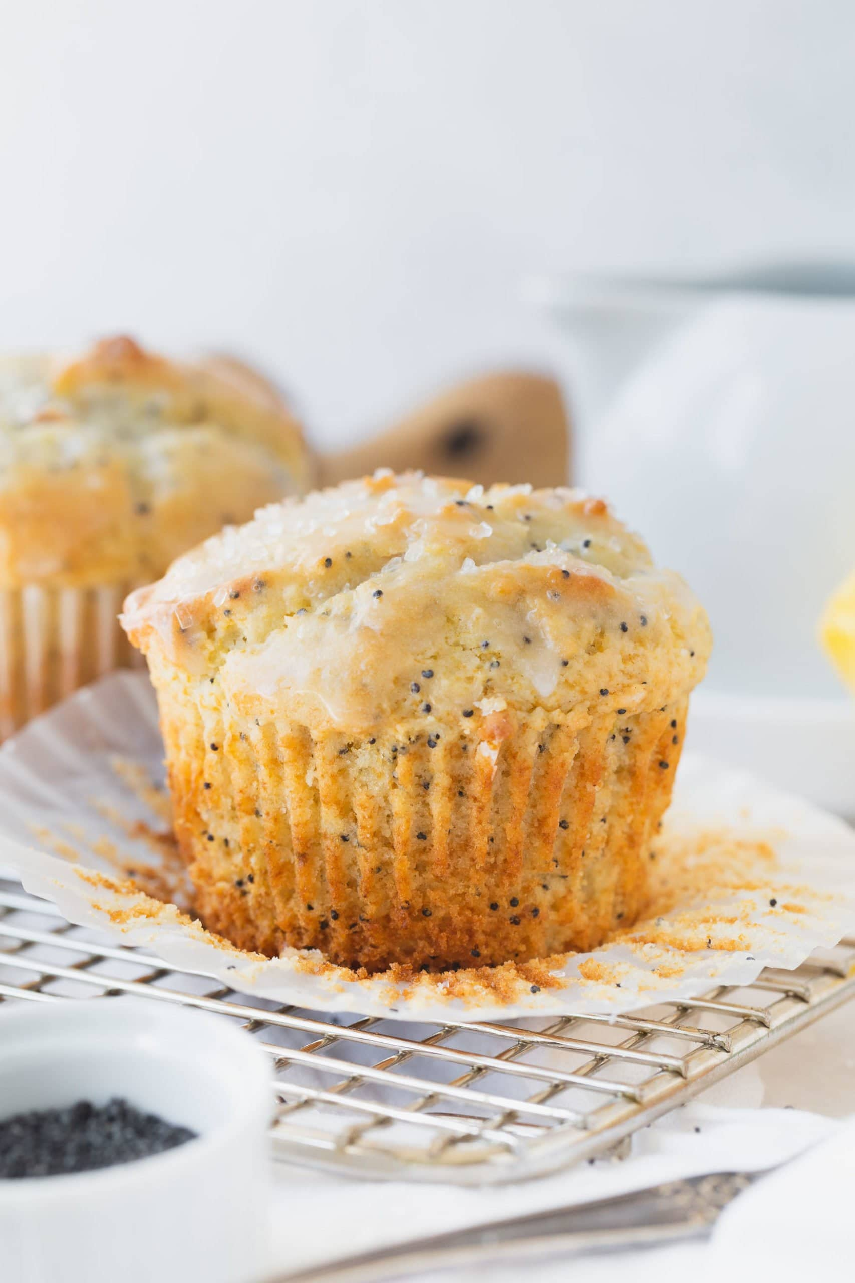 A lemon glazed lemon poppy seed muffin with the paper liner peeled back. there is another muffin in the background.