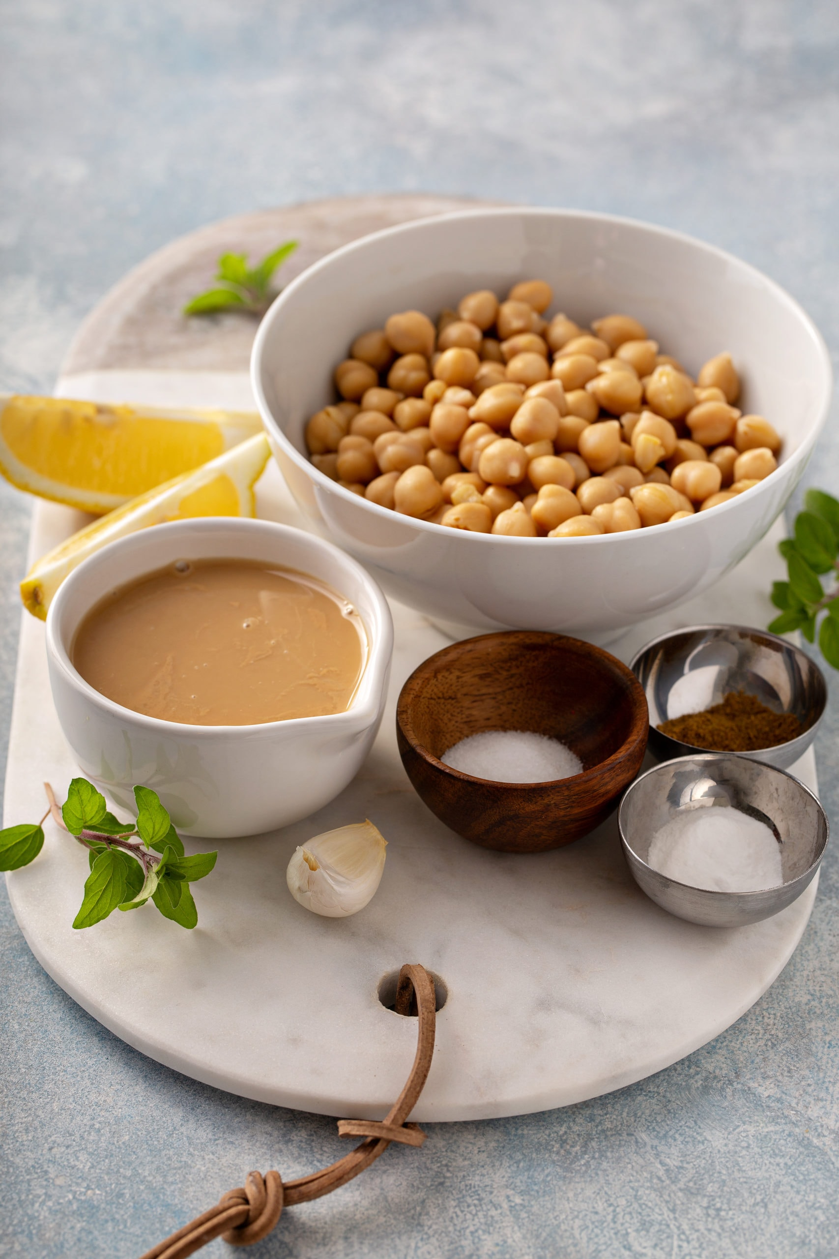 A large bowl of chick peas, smaller bowls of sea salt, cumin and baking soda with a cup of Tahini and a clove of garlic and lemon wedges.