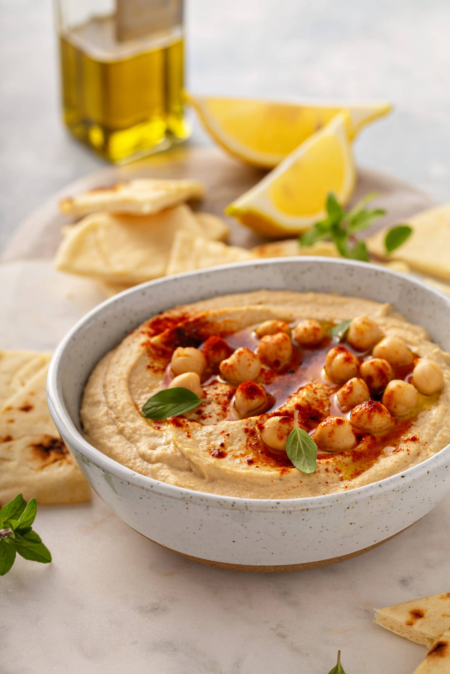A bowl of hummus with whole chick peas and smoked paprika on top, and lemon wedges and pieces of tortilla in the background.