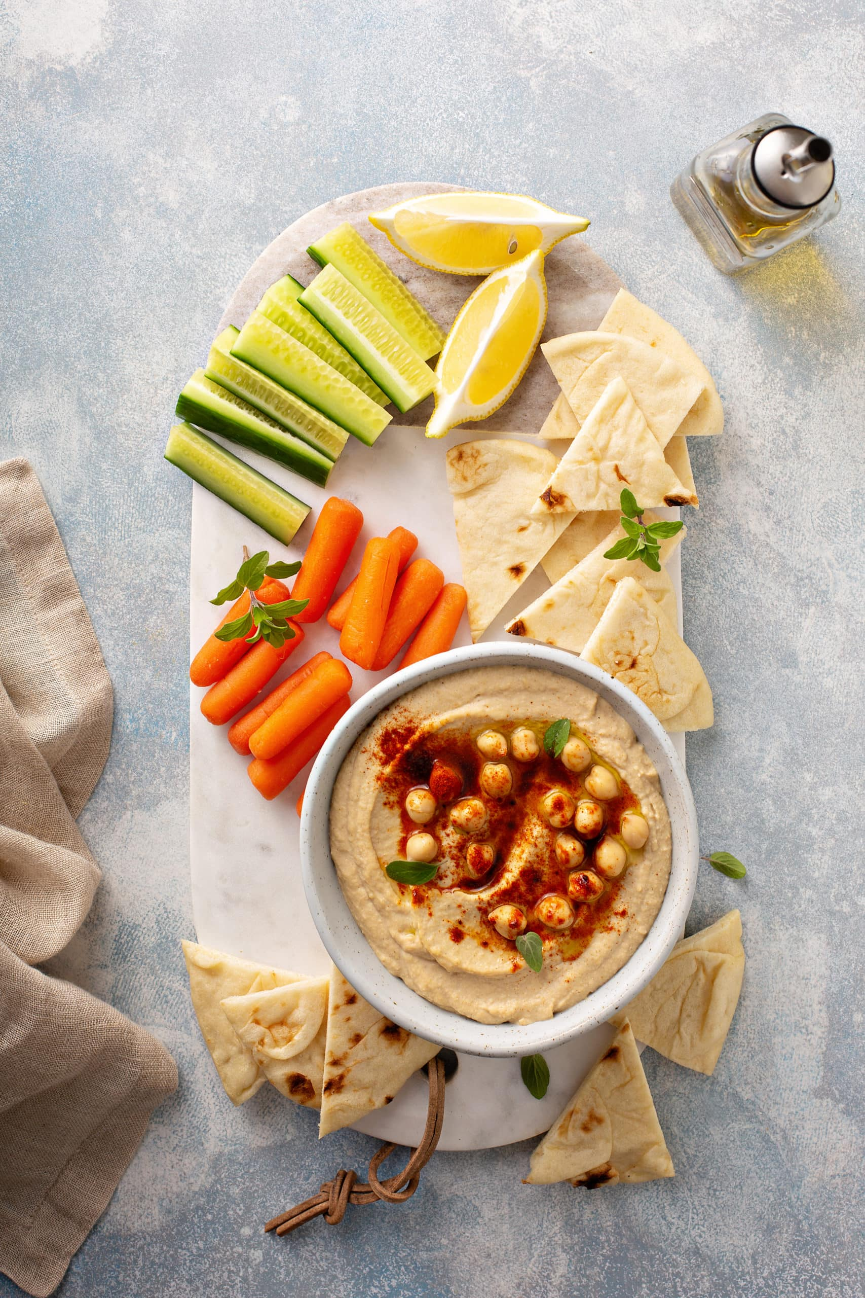 A tray with baby carrots, celery sticks, lemon wedges and tortilla wedges sitting next to a bowl of hummus with whole chick peas on top and sprinkled with smoked paprika