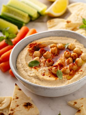 Cucumber wedges and carrot stick next to a bowl of hummus with whole chick peas on top and sprinkled with smoked paprika