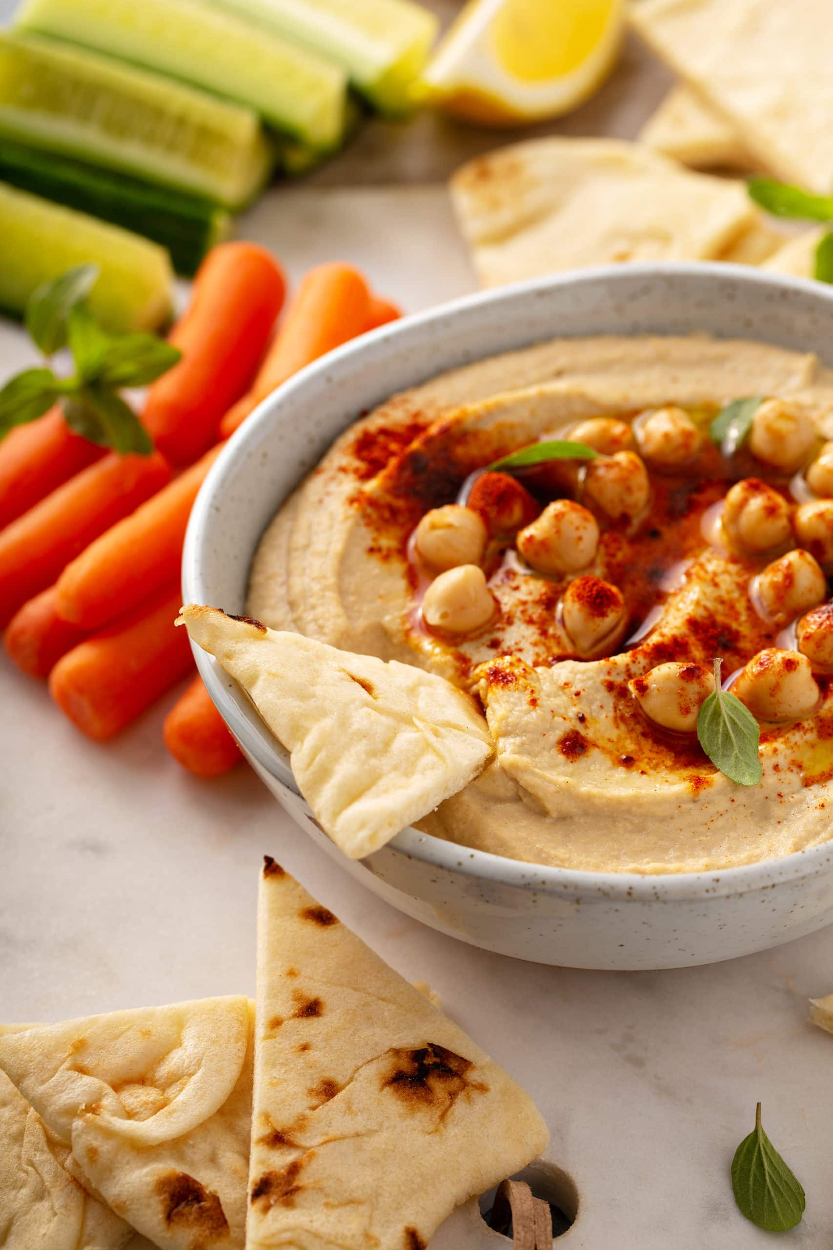 A bowl of hummus with whole chick peas on top, sprinkled with smoked paprika, and a chip dipped into it with carrot sticks on the side.